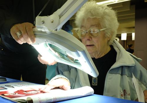 Een oudere dame test een vergrotingsloep met verlichting uit tijdens BrailleTech 2015.