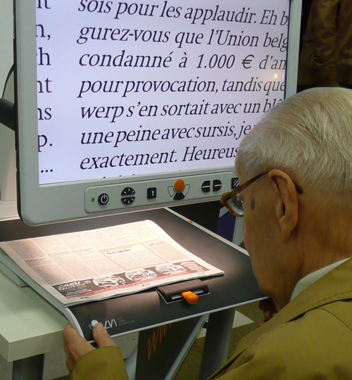 An elderly person trying out a video magnification system during the BrailleTech Exhibition.