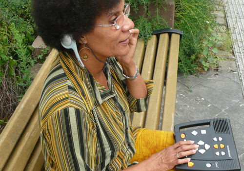 A person sitting on a bench using a Daisy player to listen to an audio book.