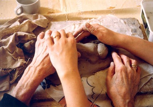 A volunteer helping a visually impaired person handle clay as part of a BrailleClub activity.